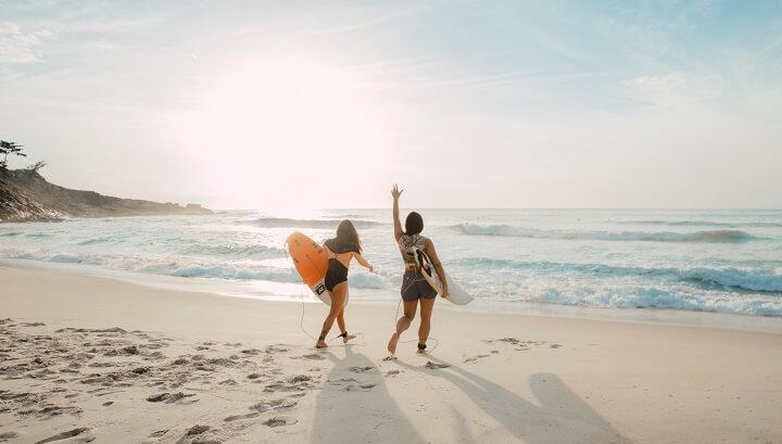 mujeres-en-la-playa-con-una-tabla-de-surf